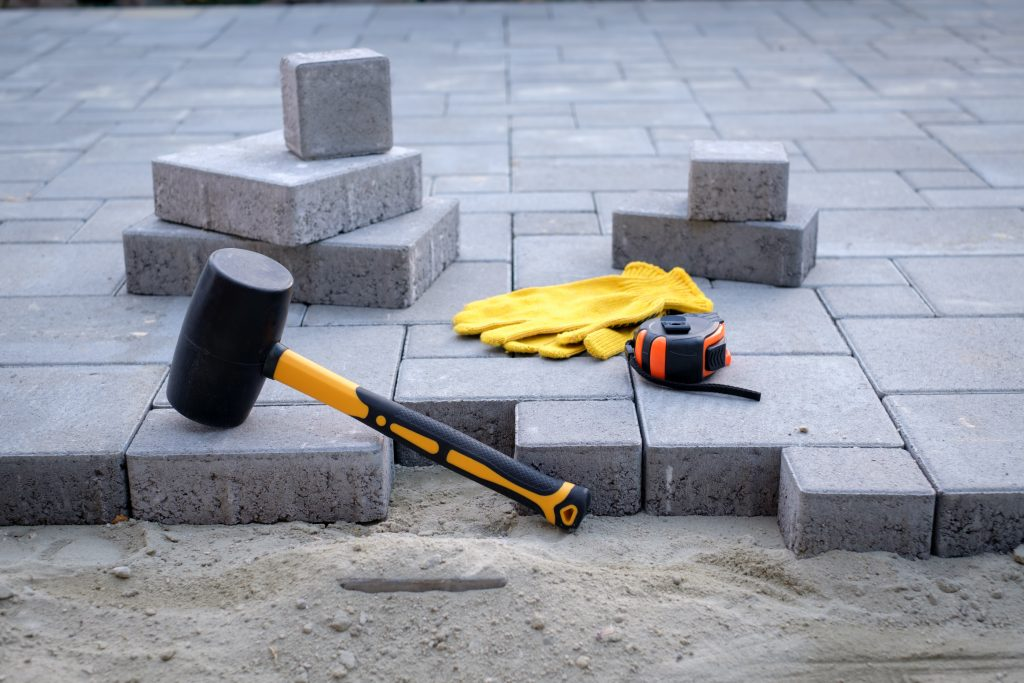 yellow gloves lays paving stones